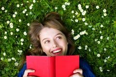 Mujer que miente en hierba con el libro Imagen de archivo libre de regalías