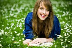 Mujer que miente en hierba con el libro Imágenes de archivo libres de regalías