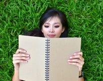 Mujer que miente en hierba con el libro Imagenes de archivo