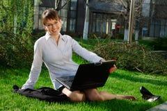 Mujer que miente en hierba con la computadora portátil Foto de archivo