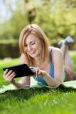 Mujer que miente en hierba con la tablilla digital Imagenes de archivo