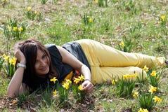 Mujer que miente en hierba con los narcisos Imagenes de archivo