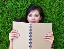 Mujer que miente en hierba con un libro Fotos de archivo libres de regalías