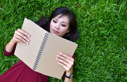 Mujer que miente en hierba verde con el libro Imagenes de archivo