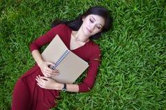 Mujer que miente en hierba verde con el libro Foto de archivo