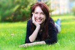 Mujer que miente en hierba verde en el prado Imagen de archivo