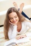 Mujer que miente en la alfombra con el libro Fotografía de archivo