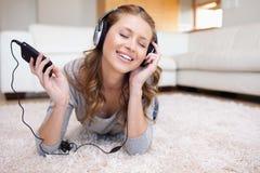 Mujer que miente en la alfombra que disfruta de música Imagen de archivo