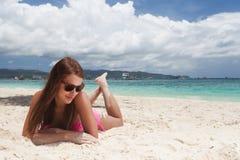 Mujer que miente en la arena en la playa Imagenes de archivo