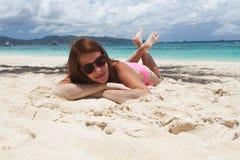 Mujer que miente en la arena en la playa Foto de archivo libre de regalías