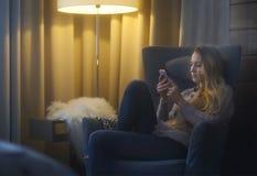 Mujer que miente en la butaca mientras que escribe un mensaje de texto en su célula Foto de archivo libre de regalías