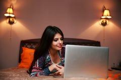mujer que miente en la cama con la computadora portátil Foto de archivo