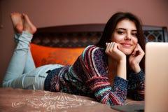 mujer que miente en la cama con la computadora portátil Fotos de archivo