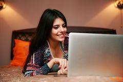 mujer que miente en la cama con la computadora portátil Imagenes de archivo