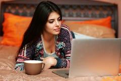 Mujer que miente en la cama con la taza de café Imágenes de archivo libres de regalías