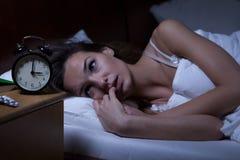 Mujer que miente en la cama insomne Fotos de archivo