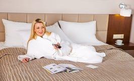 Mujer que miente en la cama que ve la TV Fotos de archivo libres de regalías
