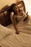 Mujer que miente en la cama, sufriendo de soledad Imagenes de archivo
