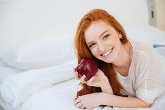 Mujer que miente en la cama y que sostiene la manzana roja Imágenes de archivo libres de regalías