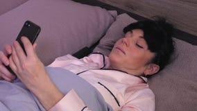 Mujer que miente en la cama y tomar selfies almacen de metraje de vídeo