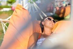 Mujer que miente en la hamaca Día asoleado caliente Mujer que se relaja en la hamaca Primer de una mujer feliz joven que miente e imagenes de archivo