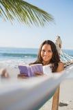 Mujer que miente en la hamaca que sostiene el libro y que sonríe en la cámara Imagen de archivo