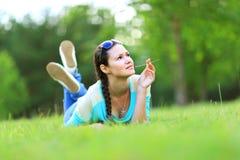 Mujer que miente en la hierba en la puesta del sol del verano Fotografía de archivo