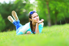 Mujer que miente en la hierba en la puesta del sol del verano Imagen de archivo libre de regalías