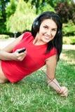 Mujer que miente en la hierba que escucha la música Imagen de archivo