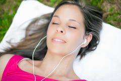 Mujer que miente en la hierba que escucha la música al aire libre fotos de archivo