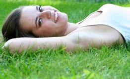 Mujer que miente en la hierba, sonriendo Imagen de archivo