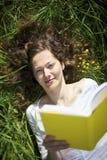 Mujer que miente en la lectura del prado Fotos de archivo libres de regalías