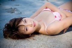 Mujer que miente en la playa Fotografía de archivo