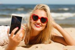 Mujer que miente en la playa arenosa usando el teléfono celular imagenes de archivo