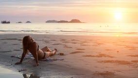 Mujer que miente en la playa en el sol poniente fotografía de archivo