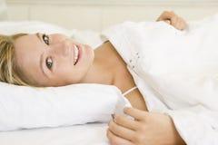 Mujer que miente en la sonrisa de la cama Imagen de archivo