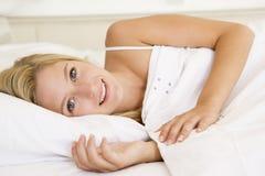 Mujer que miente en la sonrisa de la cama Foto de archivo