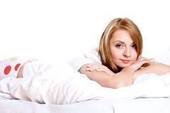 Mujer que miente en la sonrisa del dormitorio imágenes de archivo libres de regalías