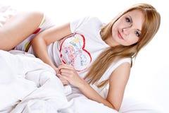 Mujer que miente en la sonrisa del dormitorio Foto de archivo