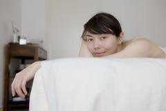 Mujer que miente en la sonrisa del dormitorio Fotos de archivo libres de regalías