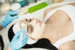 Mujer que miente en la tabla del masaje en balneario de la salud mientras que es la máscara facial Fotos de archivo libres de regalías