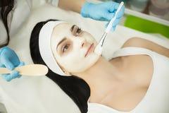 Mujer que miente en la tabla del masaje en balneario de la salud mientras que es la máscara facial Fotos de archivo