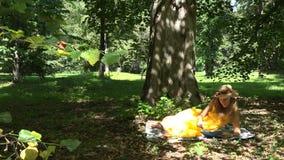 Mujer que miente en la tela escocesa y los libros de lectura en parque en día de verano soleado hermoso 4K almacen de video