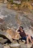 Mujer que miente en las rocas fotografía de archivo