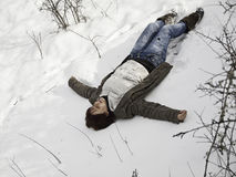 Mujer que miente en nieve Imagen de archivo