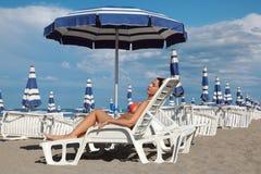 Mujer que miente en ocioso bajo el parasol de playa Foto de archivo libre de regalías