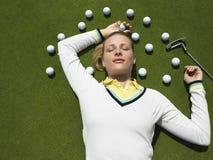 Mujer que miente en putting green con las pelotas de golf foto de archivo libre de regalías