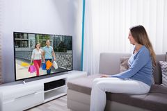Mujer que miente en Sofa Watching Television fotografía de archivo libre de regalías