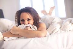 Mujer que miente en su cama que se divierte Imagen de archivo