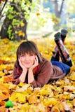Mujer que miente en su estómago en las hojas de otoño Imagenes de archivo